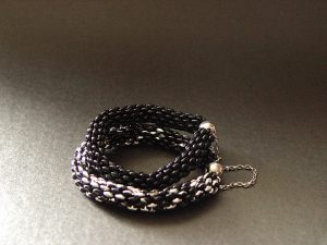 Czarna i czarno srebrna bransoletka z koralików dwu dziurkowych.